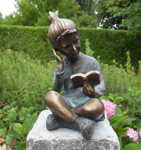 Das Mädchen Emilia mit hoch gebundenem Haar liest ein Buch als Bronzeskulptur