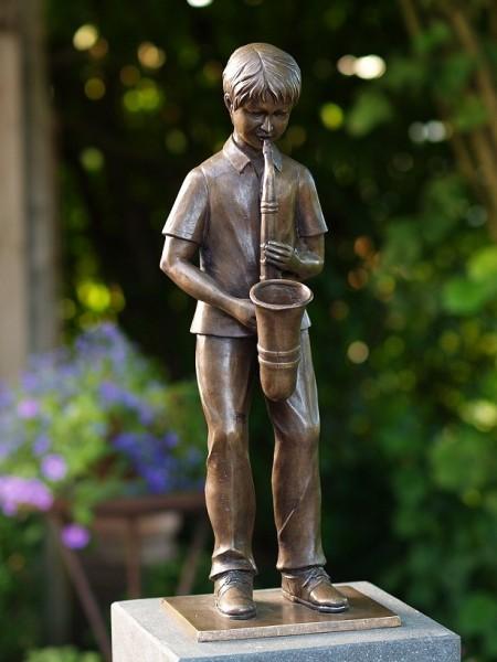 Junge Samuel spielt auf Saxophone als Bronzeskulptur