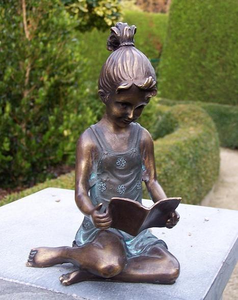 Die kleine Mia schaut ins Zeichenheft als Bronzeskulptur