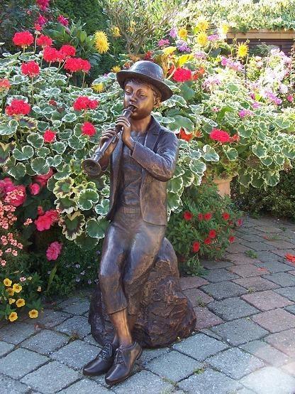 Jungen Tim sitzt auf einem Stein und spielt Flöte, als Wasserspeier Bronzeskulptur