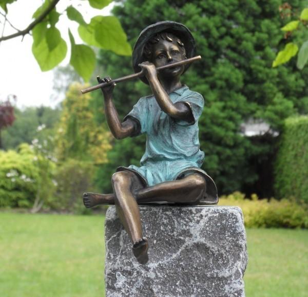 Junge spielt auf Querflöte als Bronzeskulptur